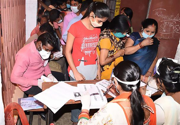 Polling officials checking the name of the voters, at a polling booth, during the first phase of the Bihar Assembly Election, at New Madhya Vidyalaya, in Gaya, Bihar on October 28, 2020.