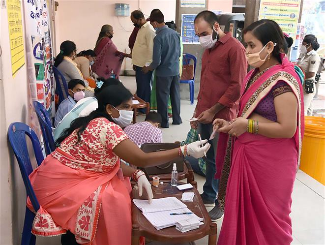 Polling officials used gloves and sanitizers while assisting the voters, at a polling booth, during the first phase of the Bihar Assembly Election, at New Madhya Vidyalaya, in Gaya, Bihar on October 28, 2020.